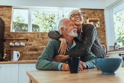 older couple smiling and hugging in kitchen